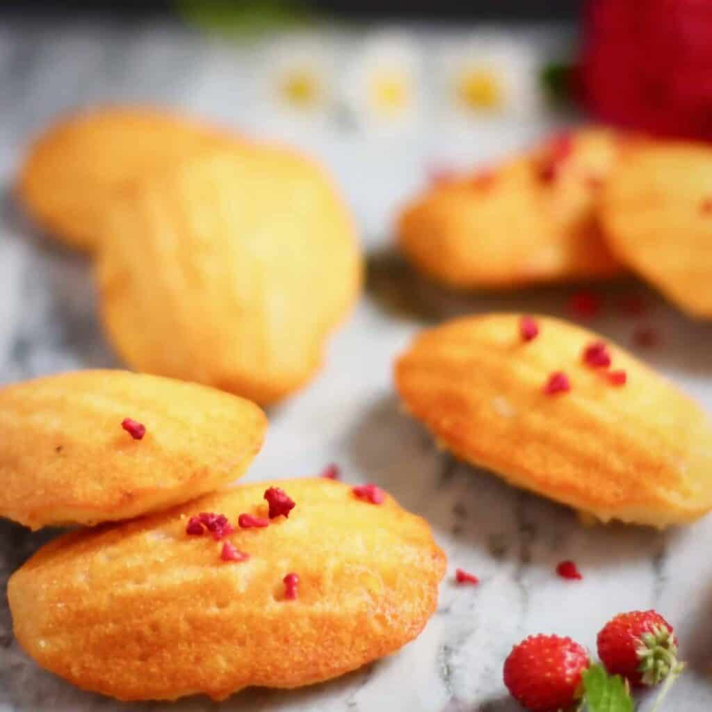 Seven madeleines on a marble background decorated with flowers against a black background