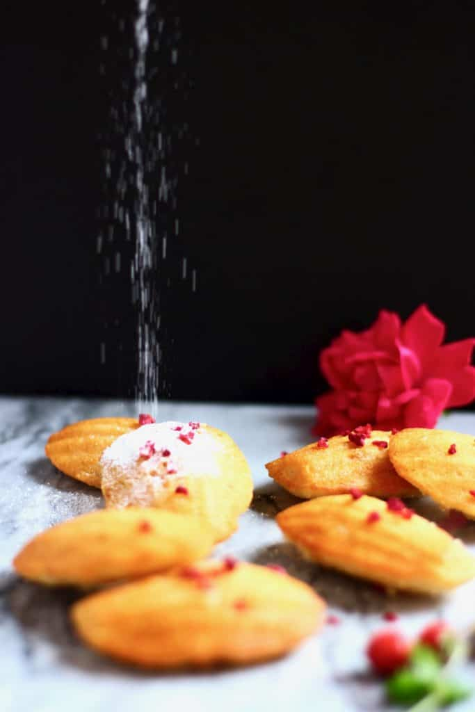 Seven madeleines on a marble background decorated with flowers against a black background with icing sugar being poured over the top