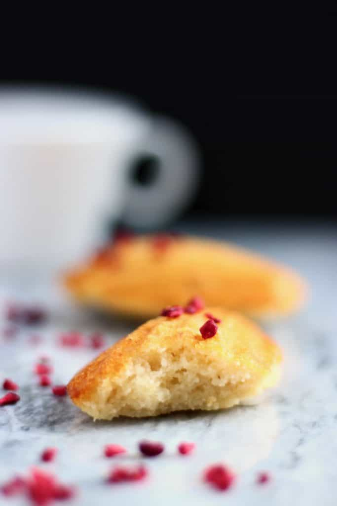 Two madeleines on a marble background with a white cup against a black background