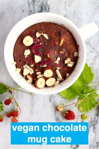 A chocolate cake in a white mug topped with chopped hazelnuts on a marble background decorated with wild strawberries