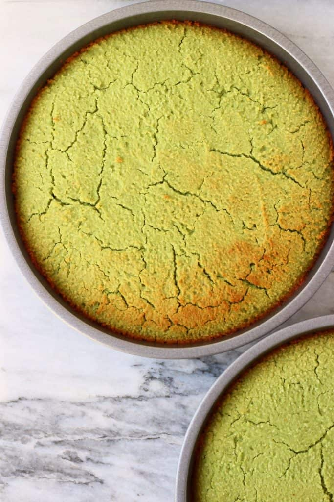 Two matcha sponge cakes in silver cake tins against a marble background