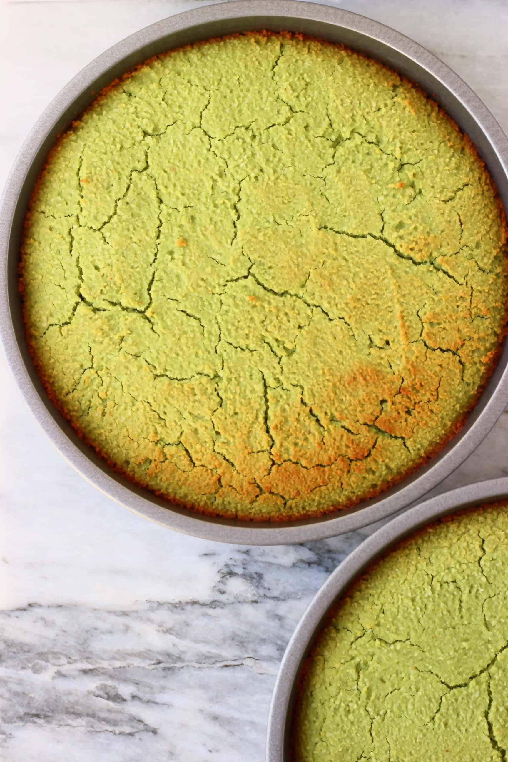 Two gluten-free vegan matcha cakes in silver baking tins
