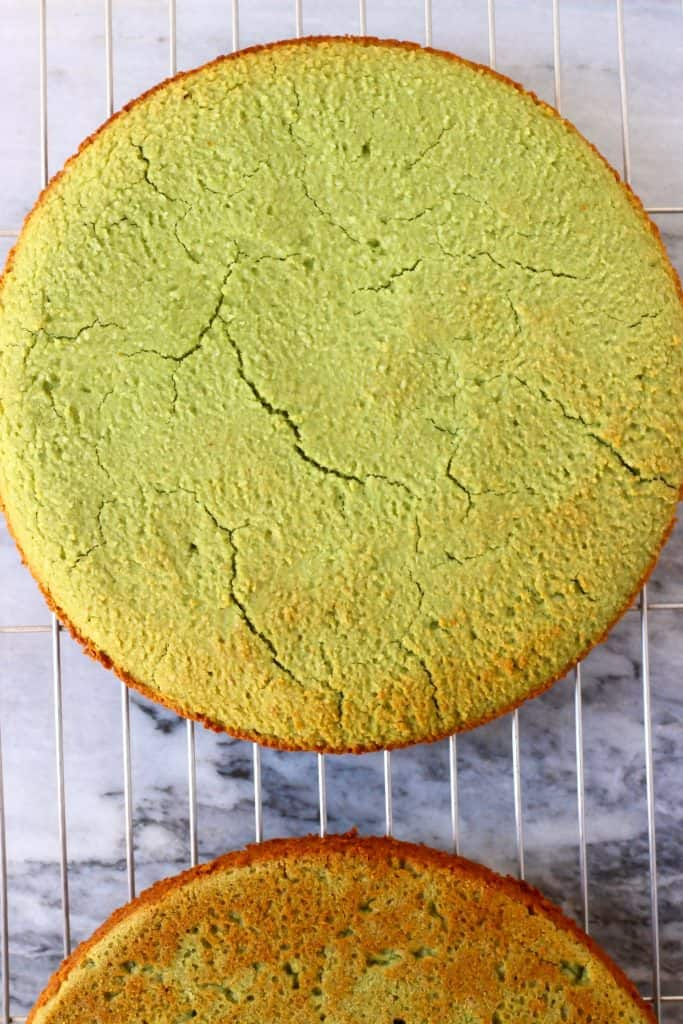Two matcha sponge cakes on a wire rack against a marble background