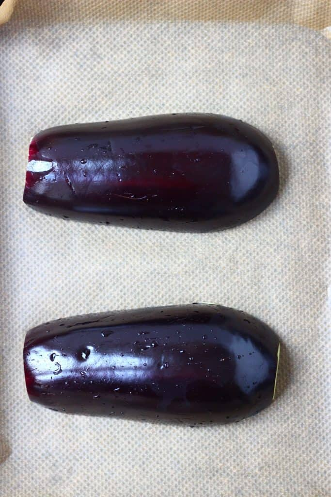Two aubergine halves lying face down on a sheet of brown baking paper