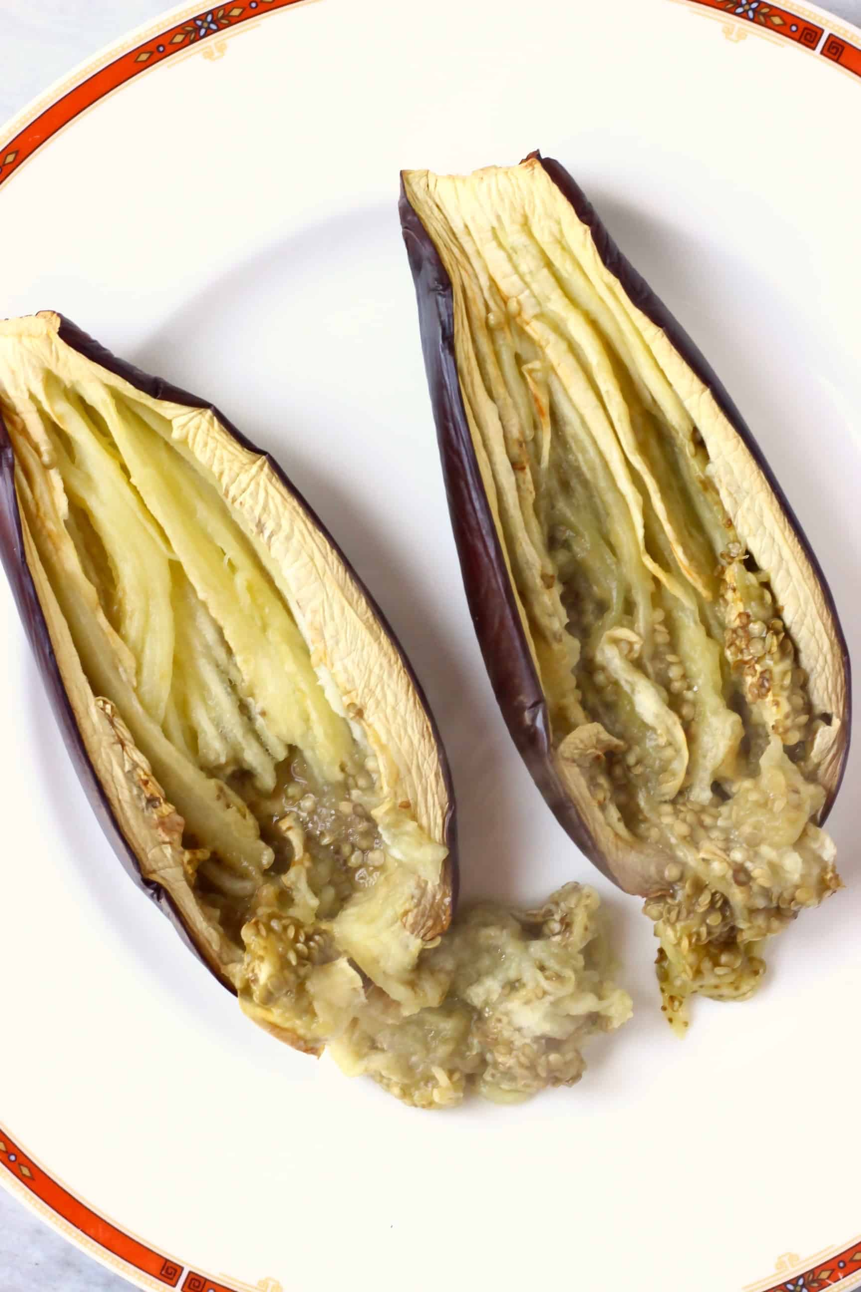 Two roasted eggplant halves being shredded on a white plate