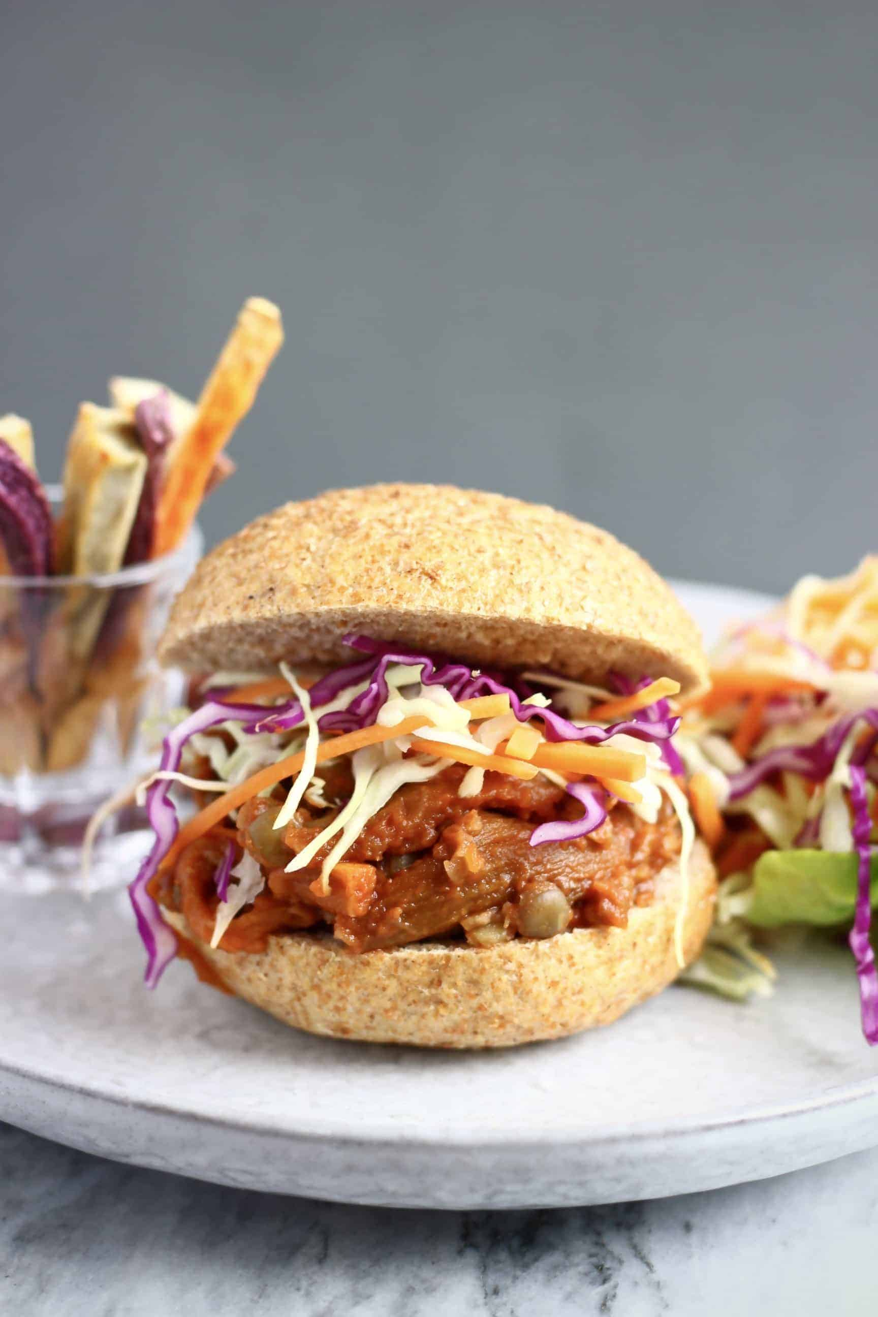 A vegan eggplant pulled pork burger with coleslaw and sweet potato fries and salad in the background