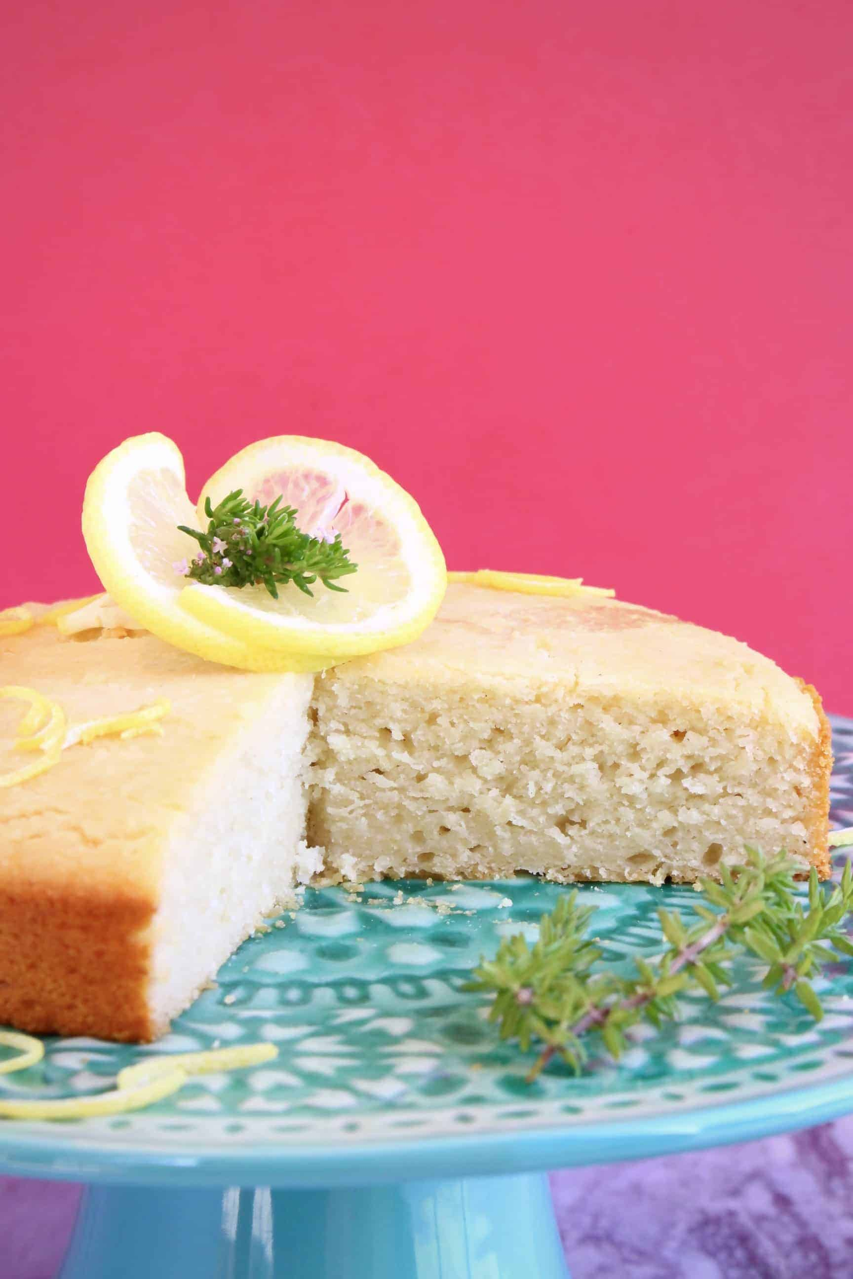 Gluten-free vegan lemon drizzle cake with a slice taken out of it on a blue cake stand with a bright pink background
