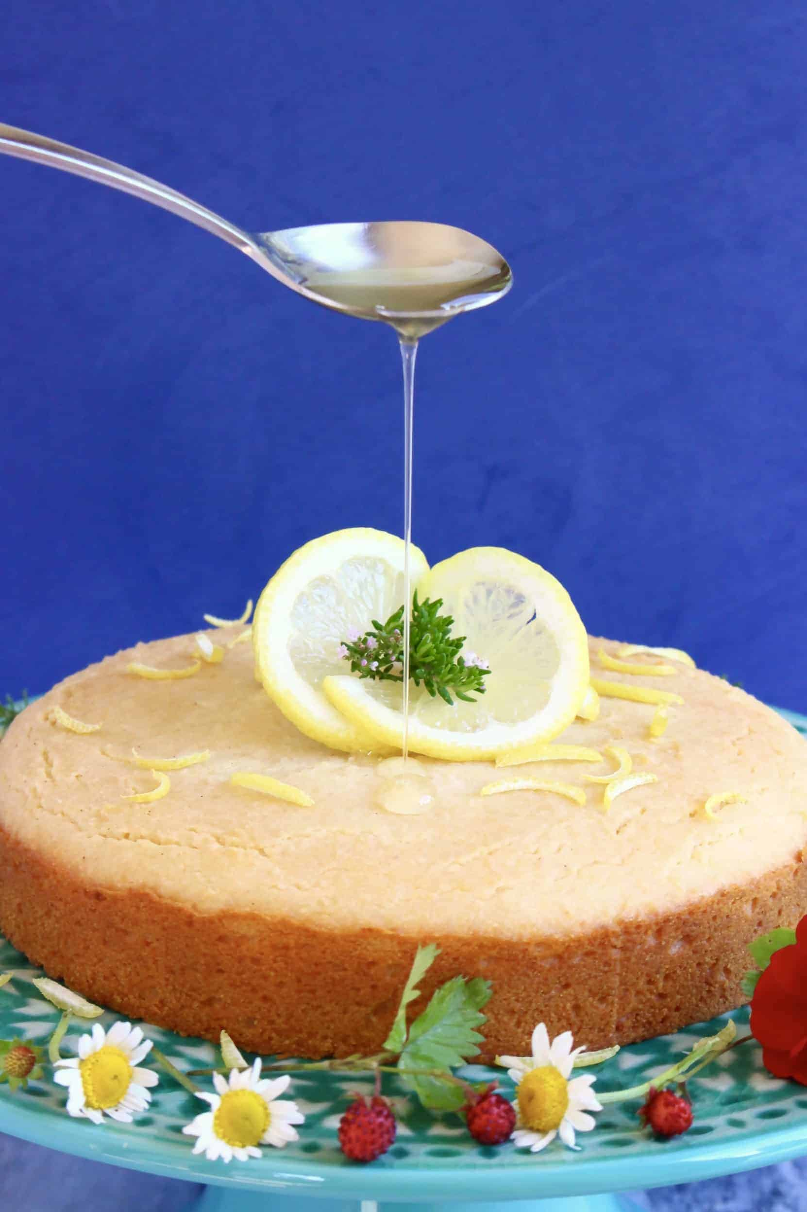 Gluten-free vegan lemon drizzle cake on a cake stand with a spoon drizzling syrup over it