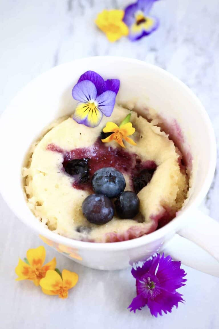 blueberry mug cake in a white cup surrounded by small flowers
