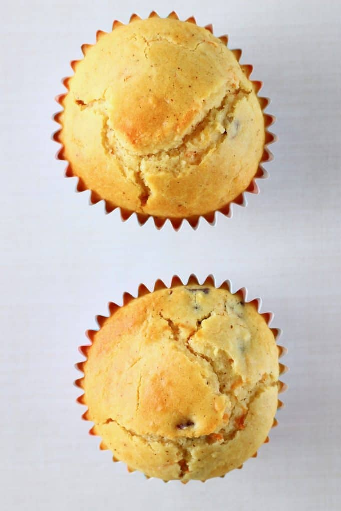 Two carrot cake cupcakes against a white background