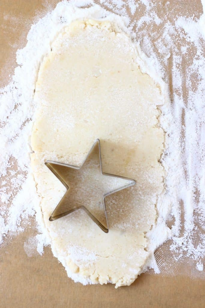Pastry dough rolled out on a piece of brown baking paper with a silver star-shaped cookie cutter cutting out star shapes