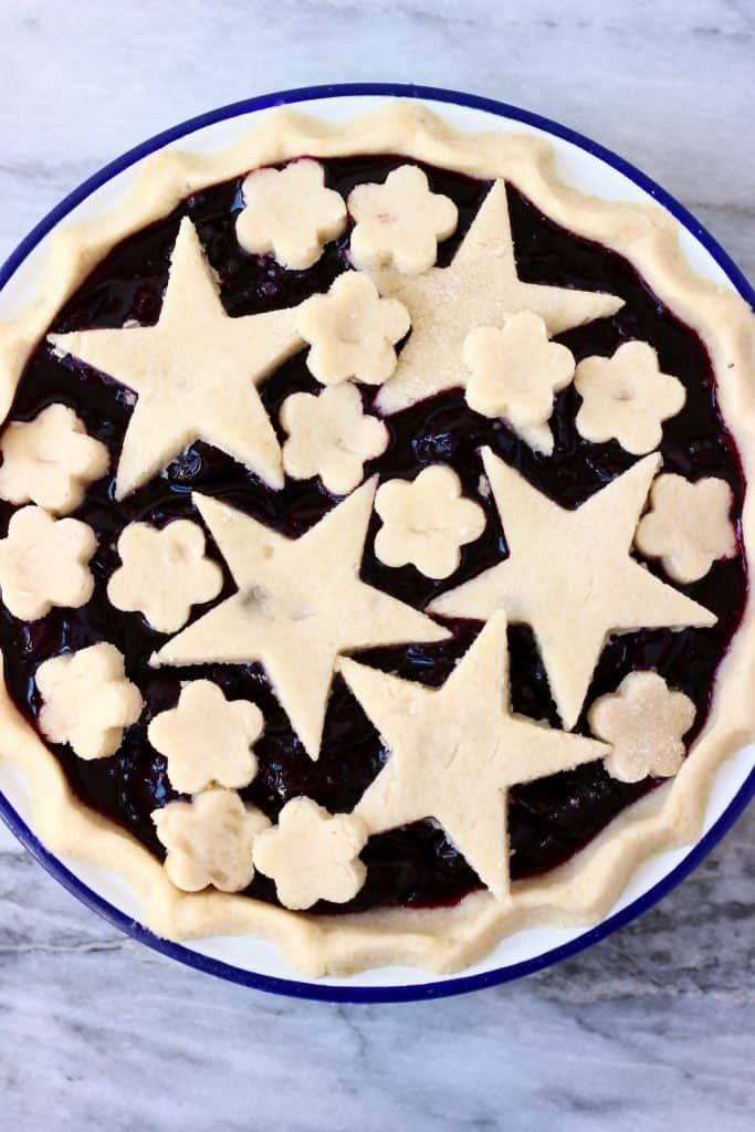 Raw cherry pie topped with stars and flowers in a white pie dish with a blue rim against a marble background