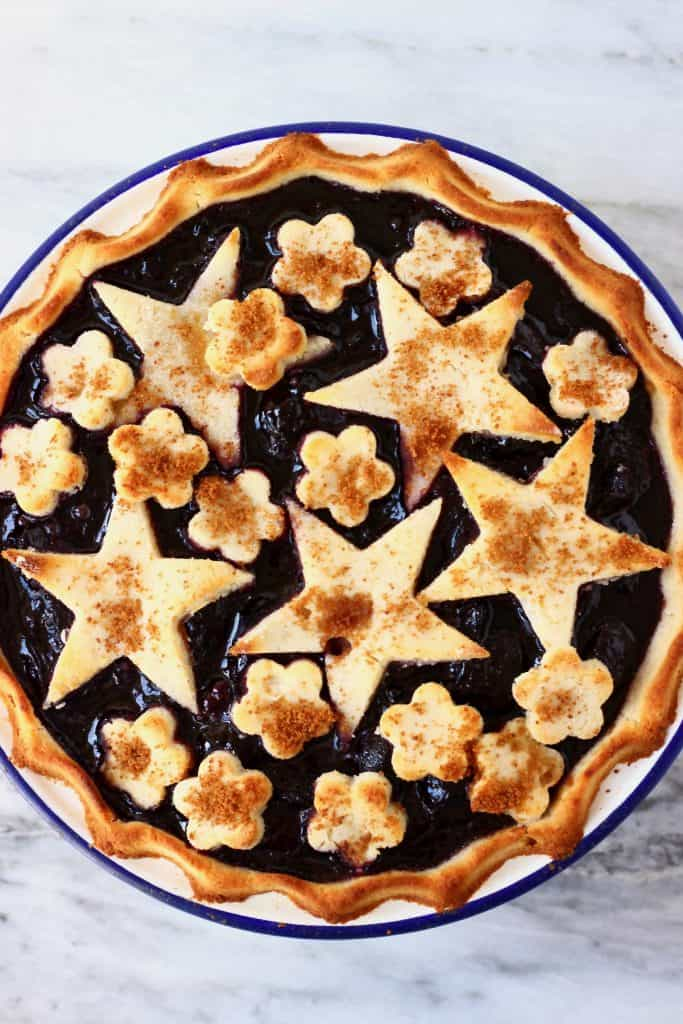 Cherry pie topped with stars and flowers in a white pie dish with a blue rim against a marble background