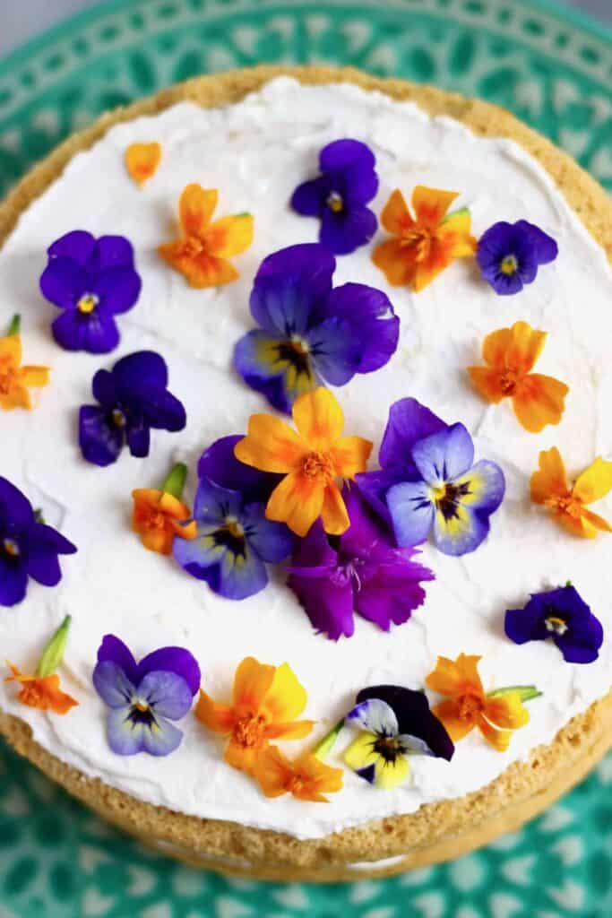 Photo of sponge cake topped with white cream frosting and orange and purple flowers on a green cake stand