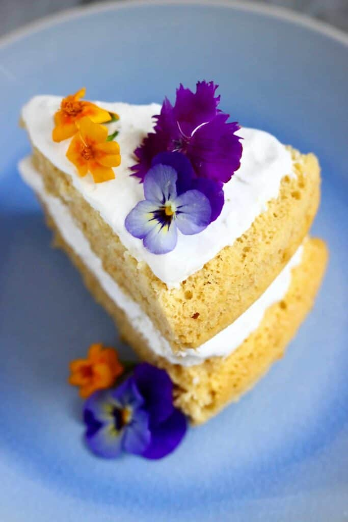 Photo of a slice of sponge cake sandwiched with white creamy frosting decorated with purple and orange flowers on a light blue plate