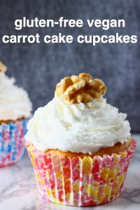 Two carrot cake cupcakes topped with creamy frosting and a walnut on a marble slab against a grey background