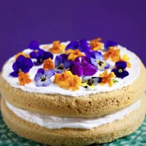 Photo of orange sponge cake sandwiched with creamy white frosting topped with orange and purple flowers on a green cake stand against a purple background