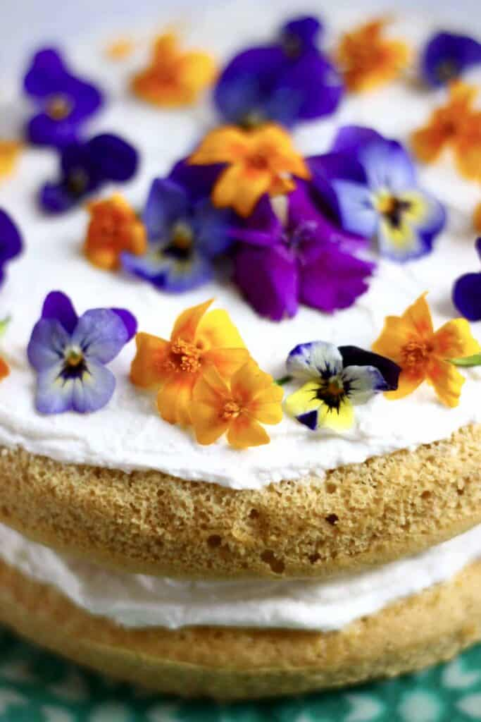 Photo of orange sponge cake sandwiched with white creamy frosting topped with purple and orange flowers