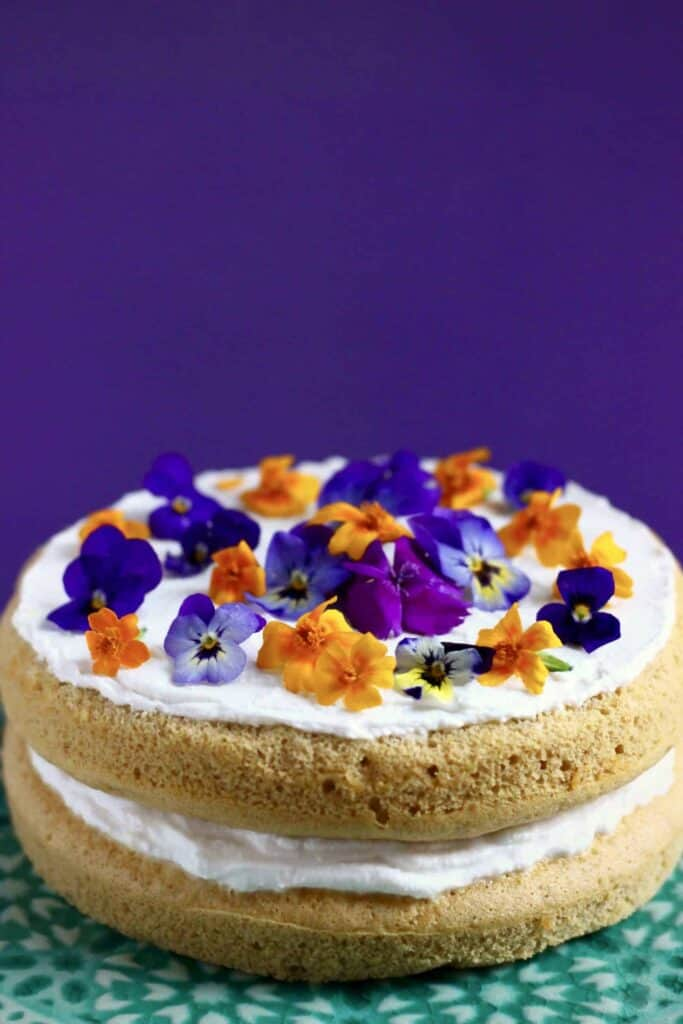 Photo Of Orange Sponge Cake Sandwiched With Creamy White Frosting Topped And Purple Flowers