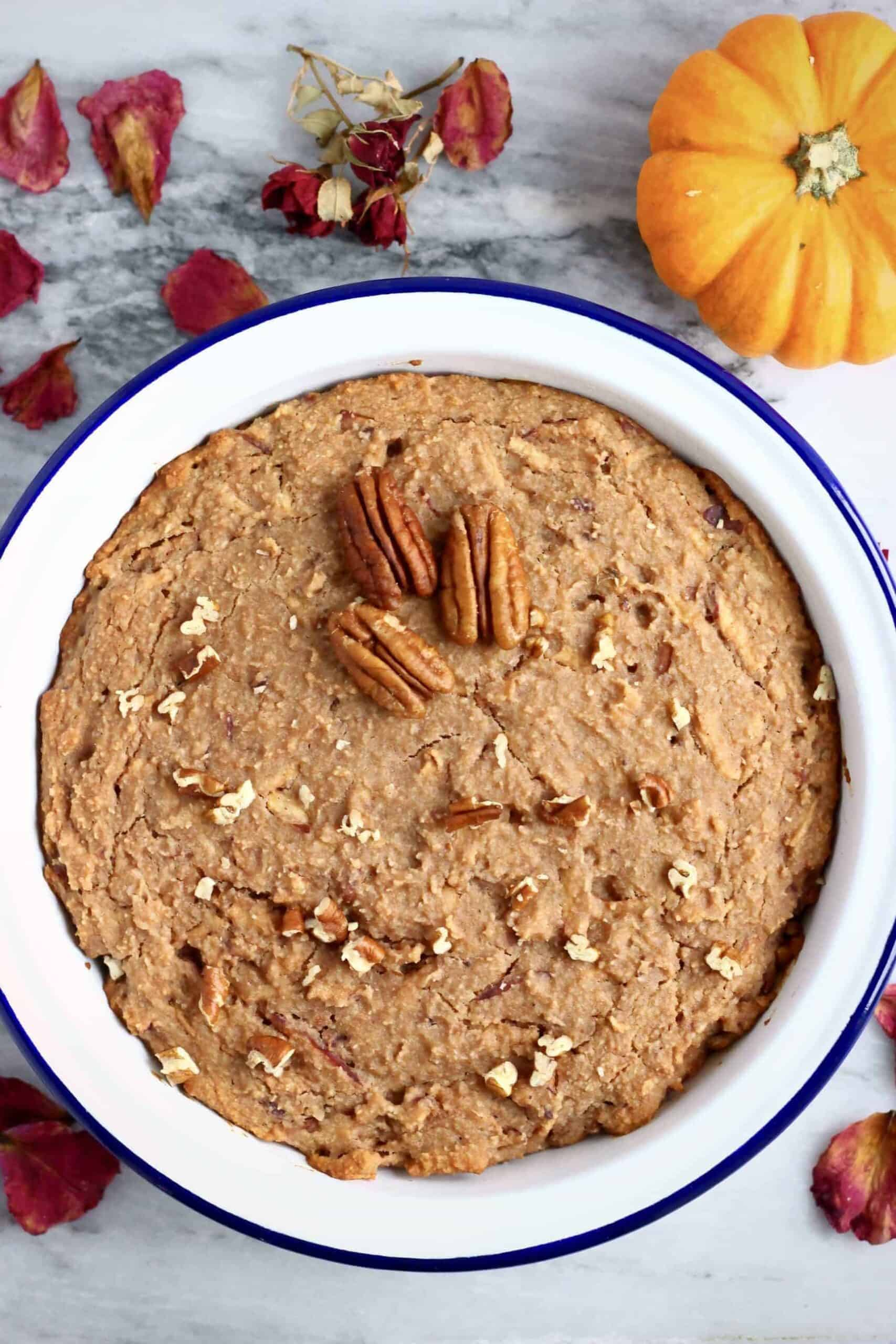 A gluten-free vegan apple cake in a round baking dish topped with chopped pecan nuts