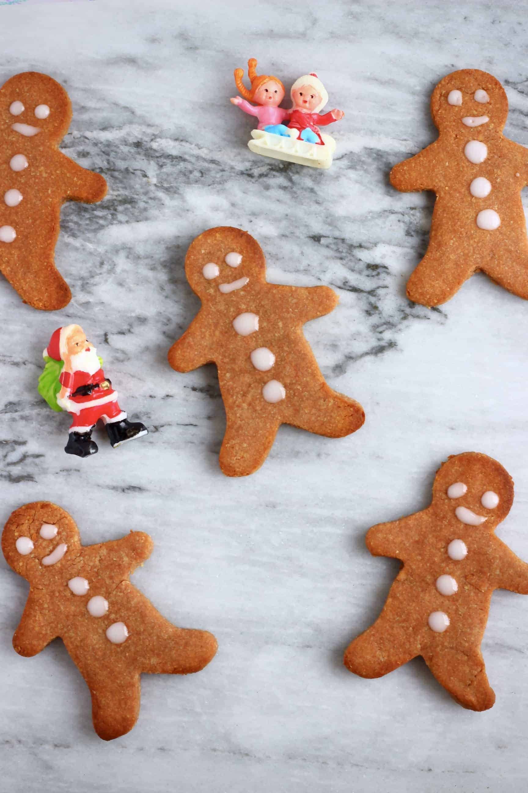 Five gluten-free vegan gingerbread cookies on a marble background