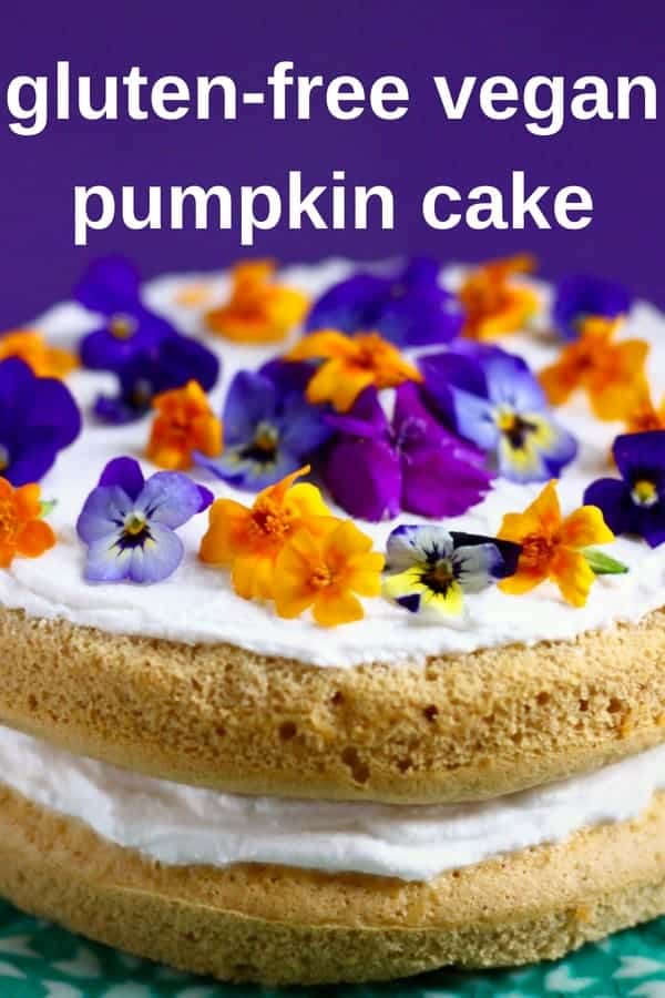 Photo of a sponge cake topped with flowers on a blue cake stand with a purple background