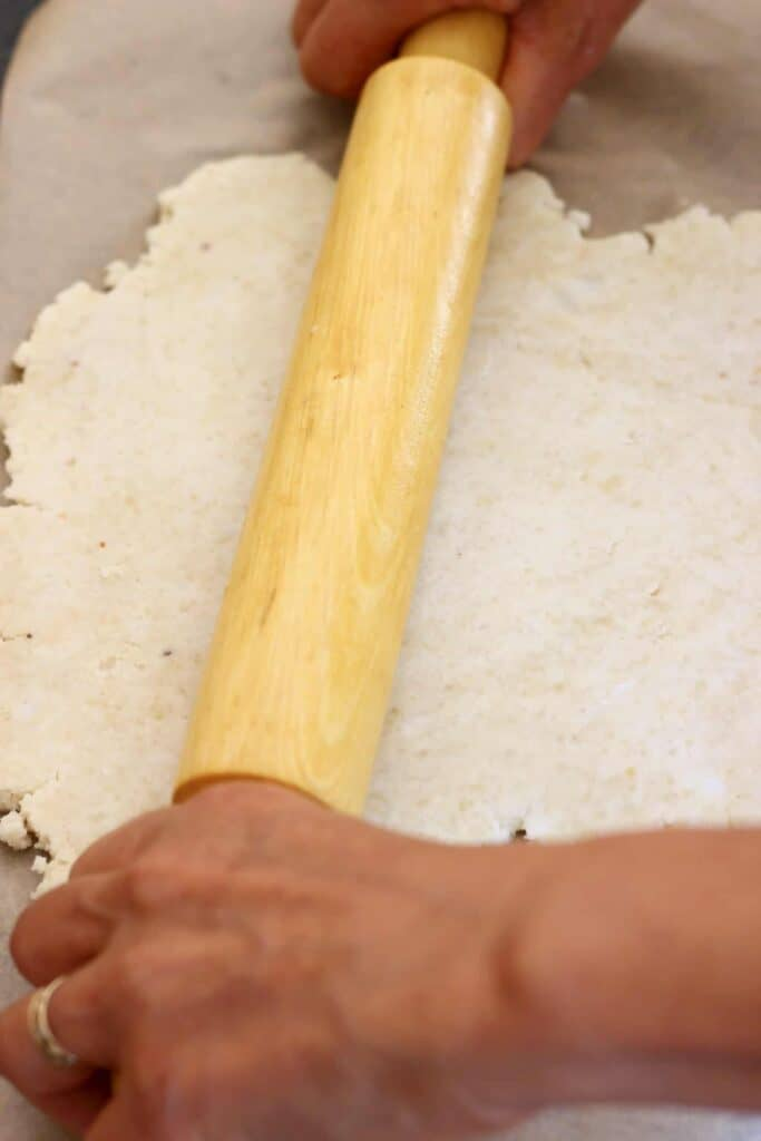 Photo of a sheet of brown baking paper topped with pastry dough with two hands and a rolling pin rolling it out
