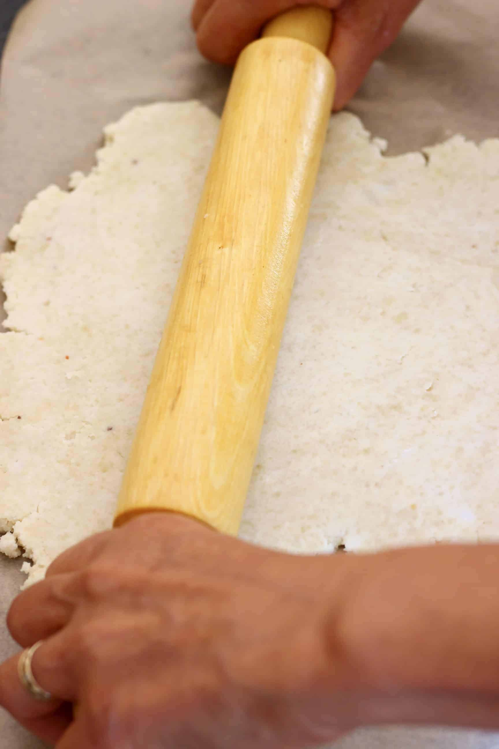A sheet of brown baking paper topped with pastry dough with two hands and a rolling pin rolling it out