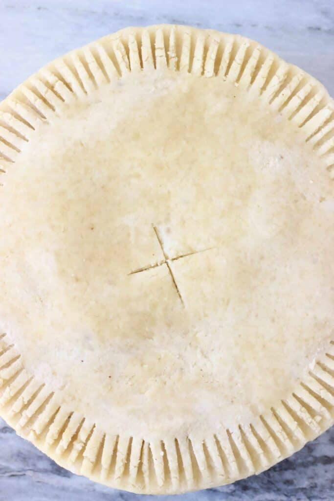 Photo of a raw pie topped with pie crust with crimped edges and a slit in the middle against a marble background