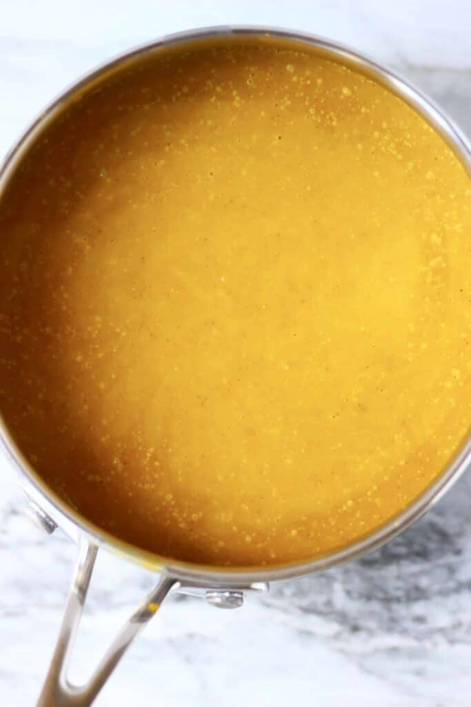 Photo of orange pumpkin pie filling in a saucepan against a marble background