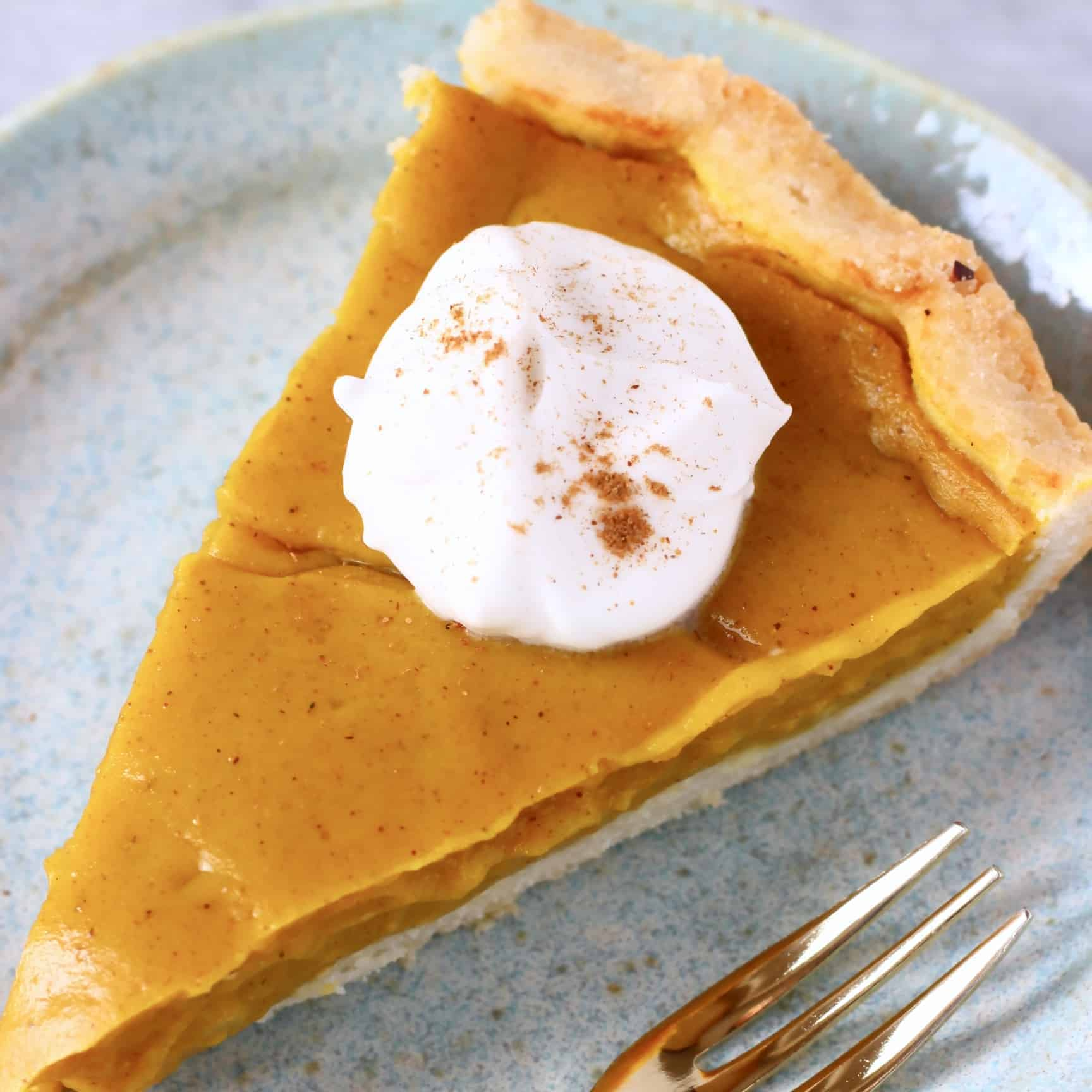A slice of gluten-free vegan pumpkin pie topped with cream on a plate with a fork