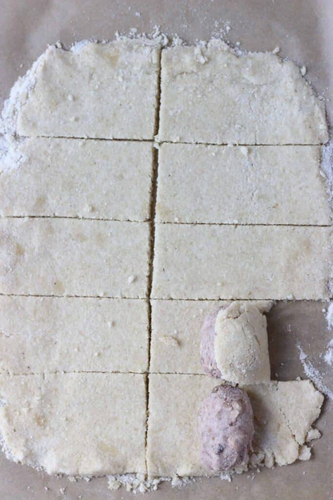 Photo of pastry rolled out and cut into ten pieces on a piece of brown baking paper with two sausages being rolled in the pastry