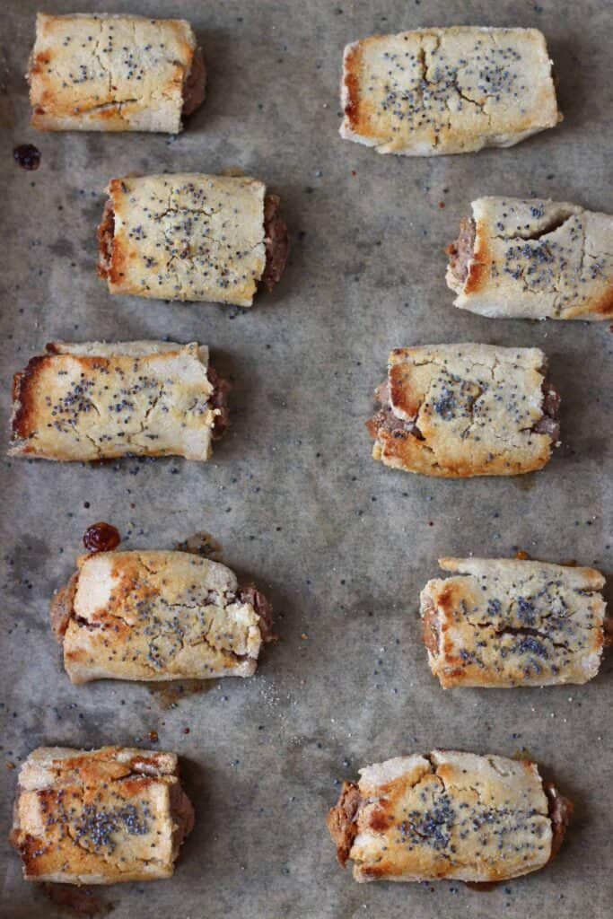 Photo of ten cooked sausage rolls sprinkled with poppy seeds on a brown baking sheet