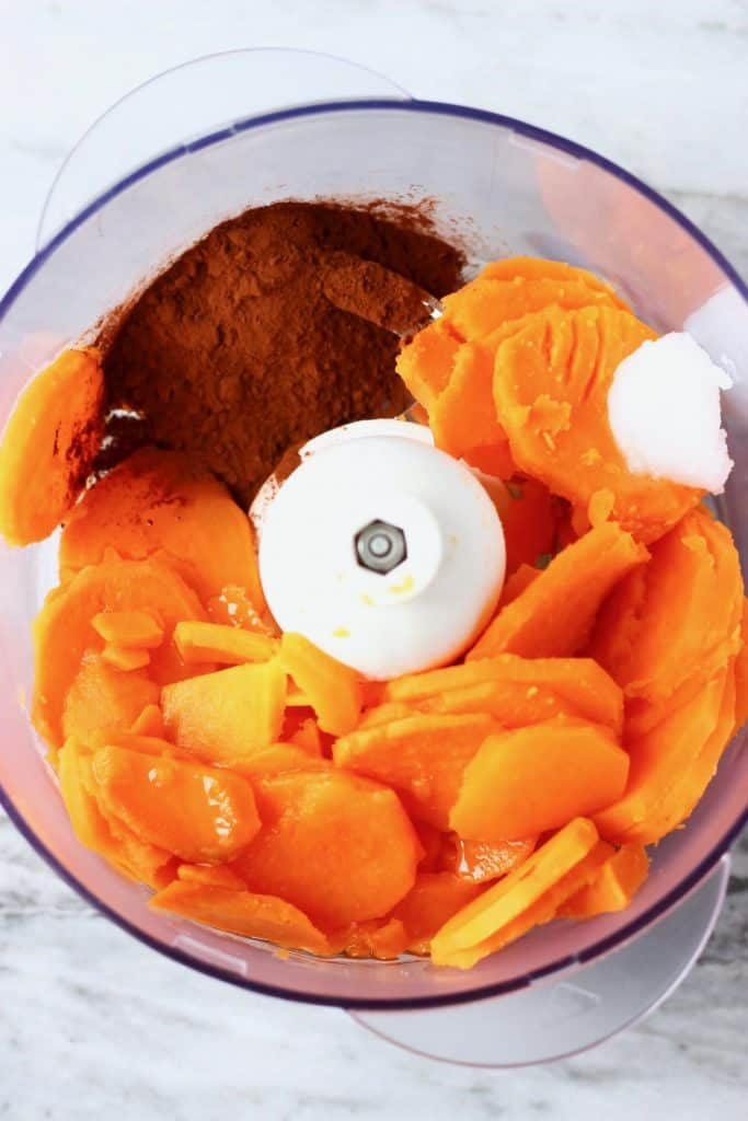 Cooked sweet potatoes, coconut oil and cocoa powder in a food processor against a marble background