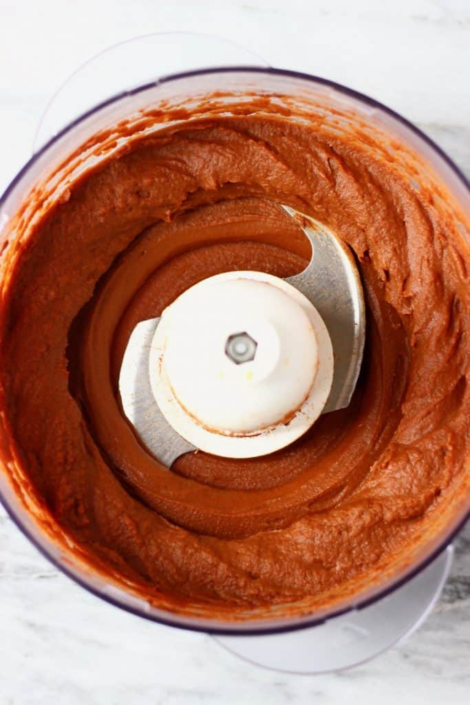 Chocolate buttercream in a food processor against a marble background