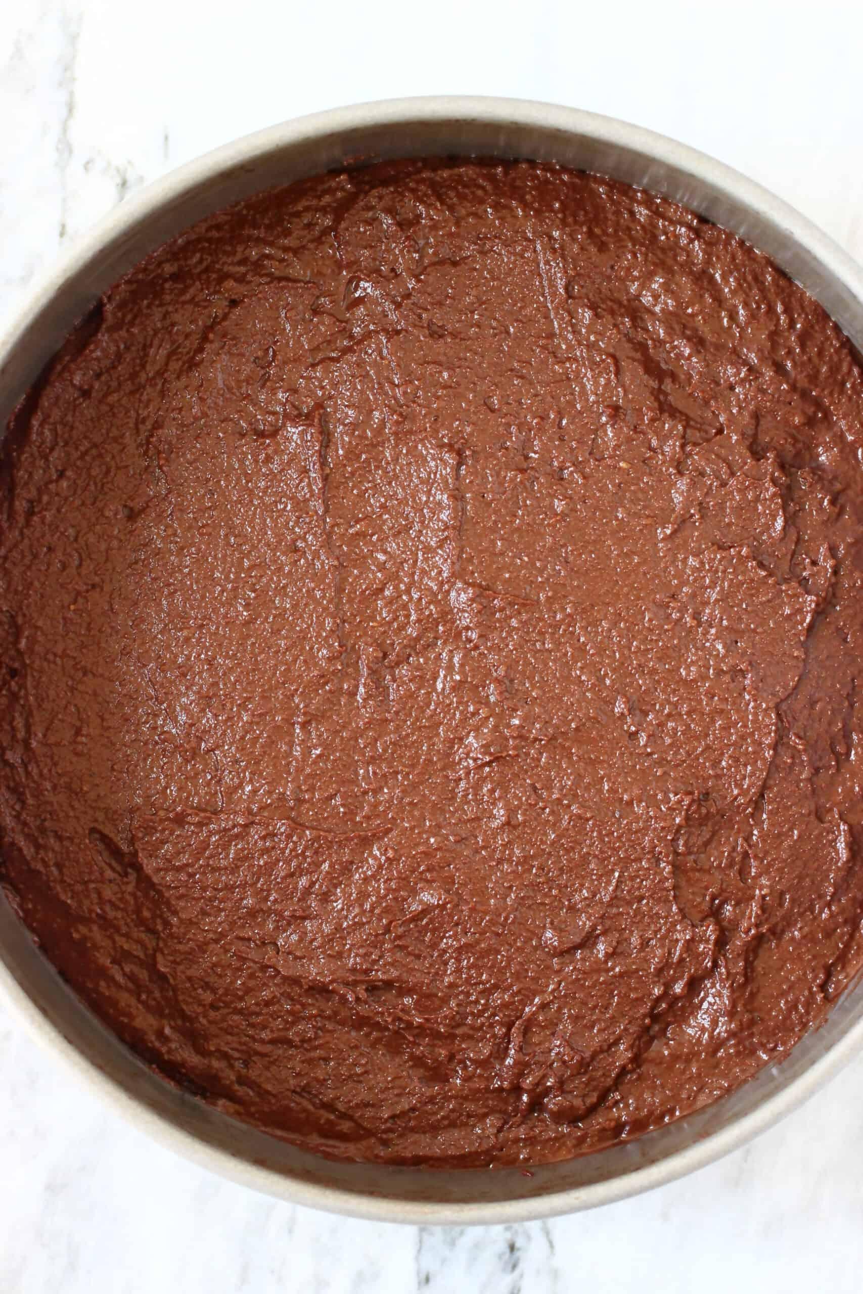 Raw gluten-free vegan chocolate mousse cake batter in a springform baking tin
