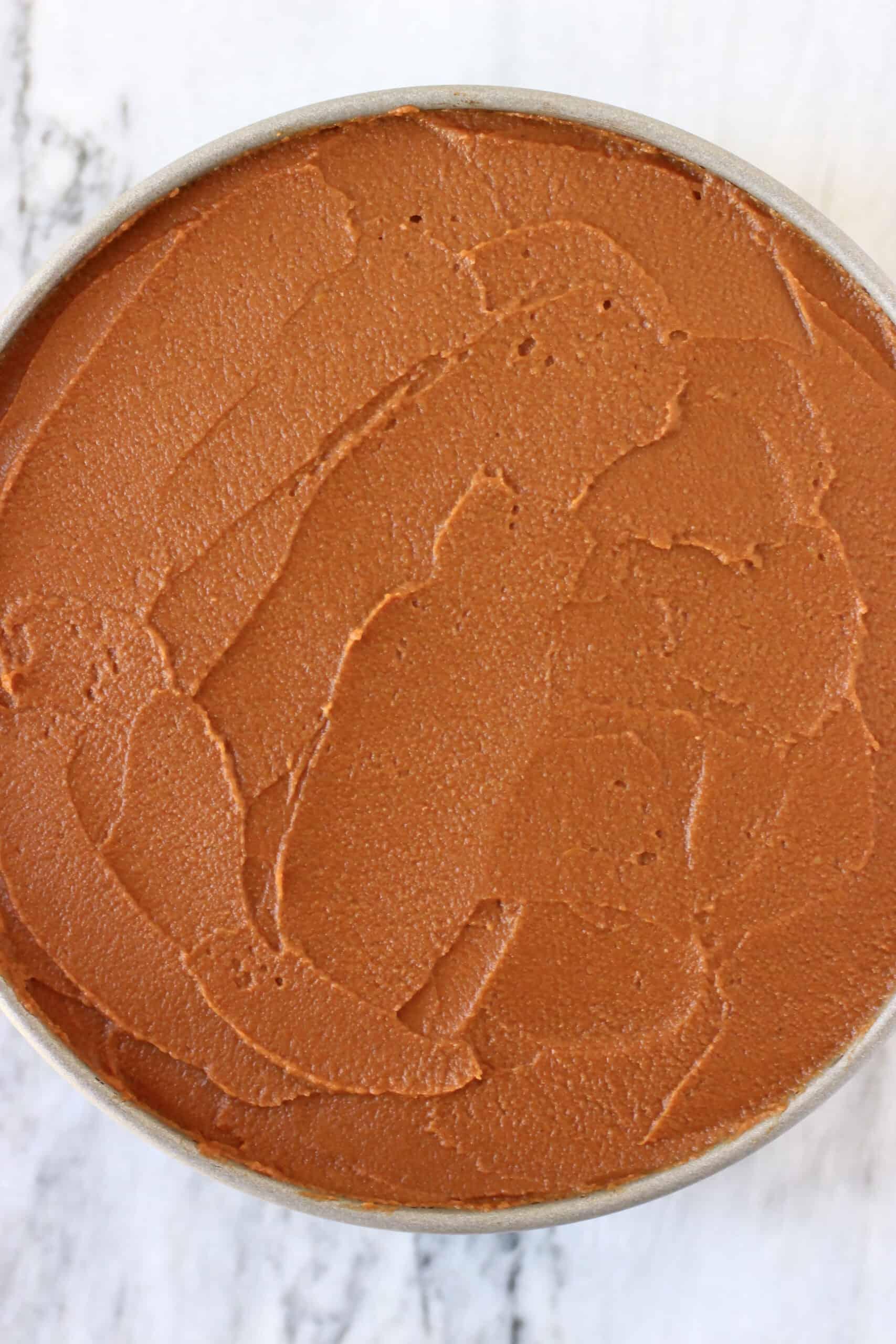 Vegan chocolate mousse on vegan chocolate sponge in a springform baking tin