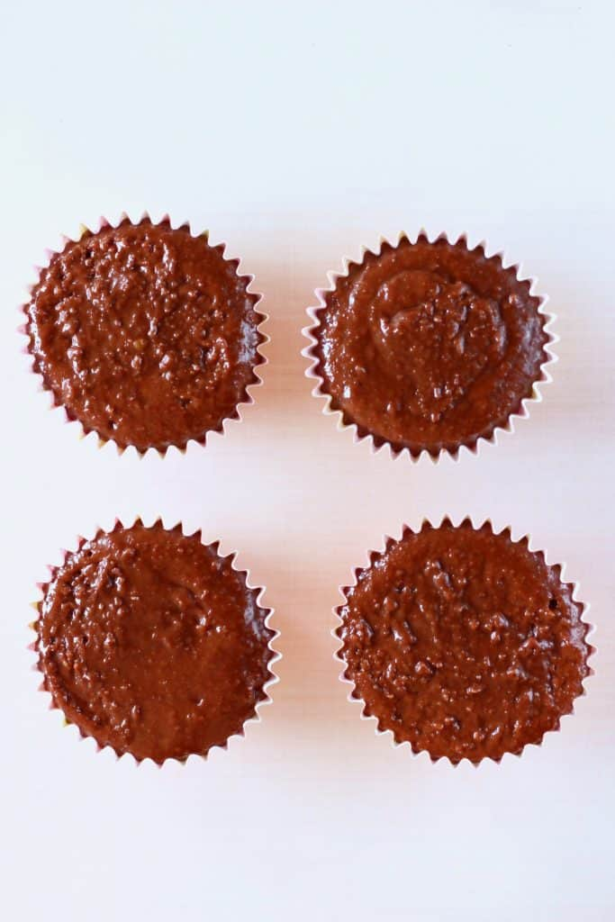 Four cupcake cases filled with raw chocolate cake batter on a white background