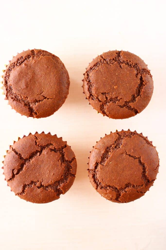 Four chocolate cupcakes on a white background