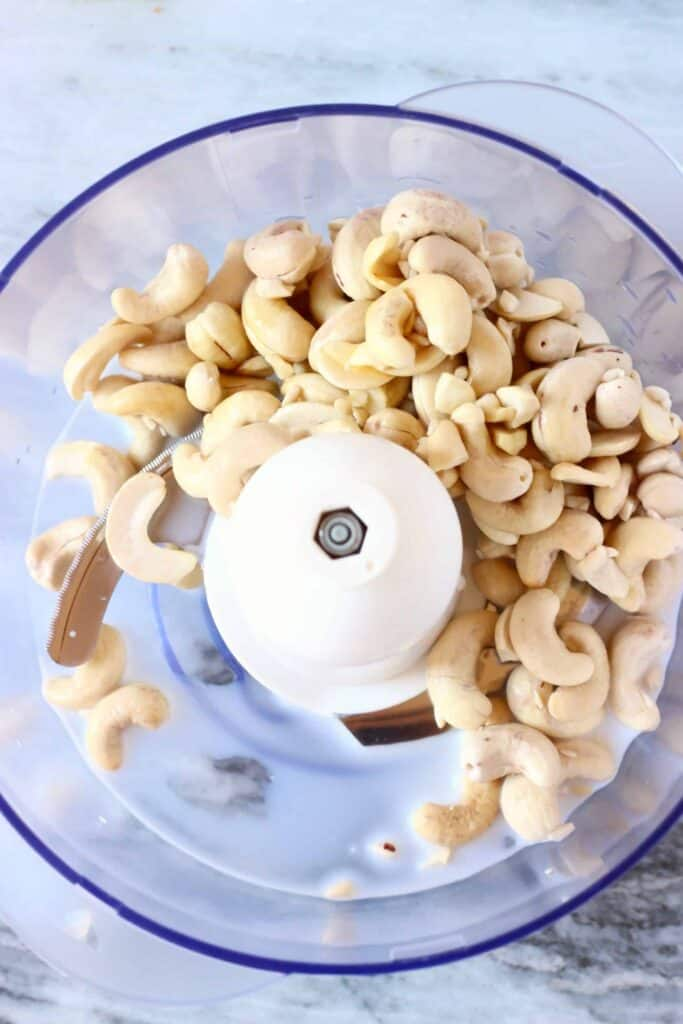 Photo of cashew nuts in a food processor against a marble background