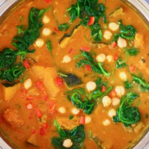 Photo of diced pumpkin, chickpeas and spinach in a yellow curry sauce in a silver saucepan