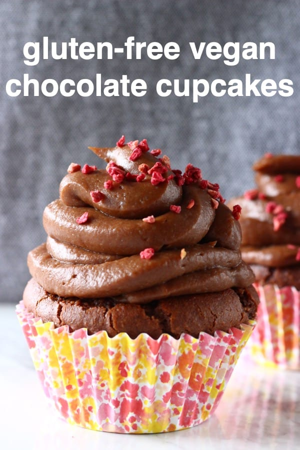 Two chocolate cupcakes in pink cupcake wrappers topped with chocolate buttercream and sprinkled with freeze-dried raspberries on a marble slab against a grey background