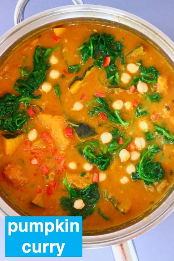 Photo of orange curry with diced pumpkin, chickpeas and spinach in a silver saucepan