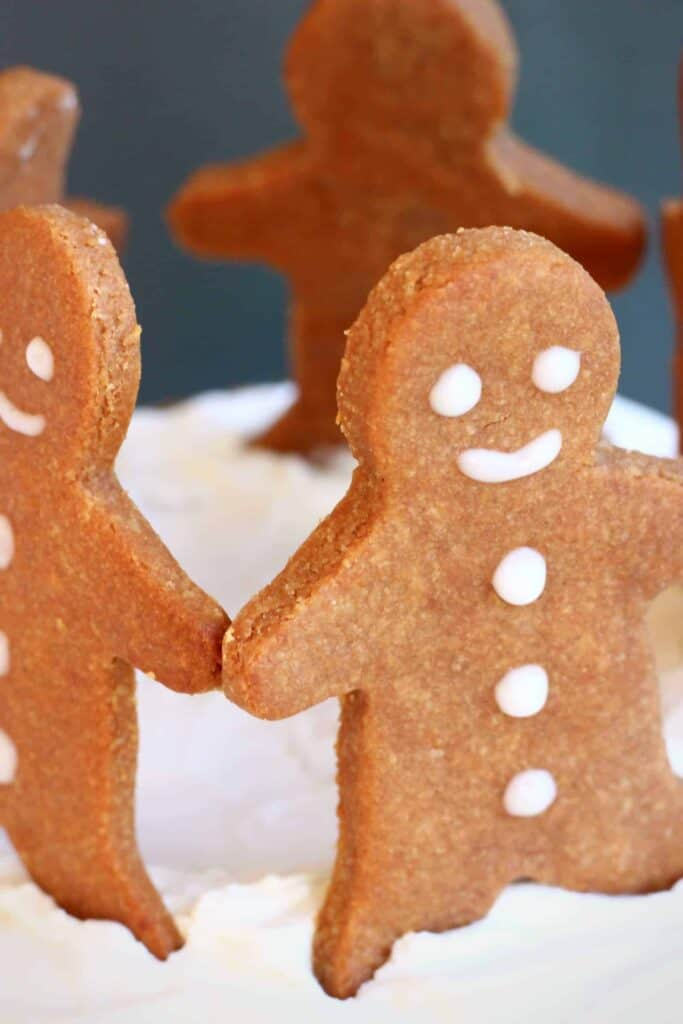 Photo of gingerbread men cookies on a bed of white creamy frosting