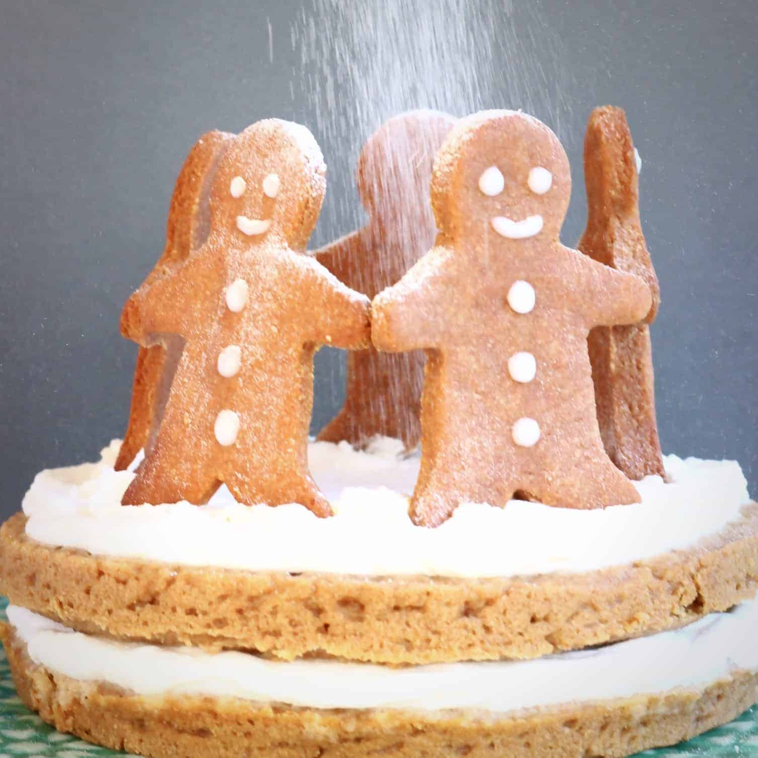 Photo of gingerbread sponge cake sandwiched with white cream topped with five gingerbread men cookies standing in a circle with a dusting of white icing sugar