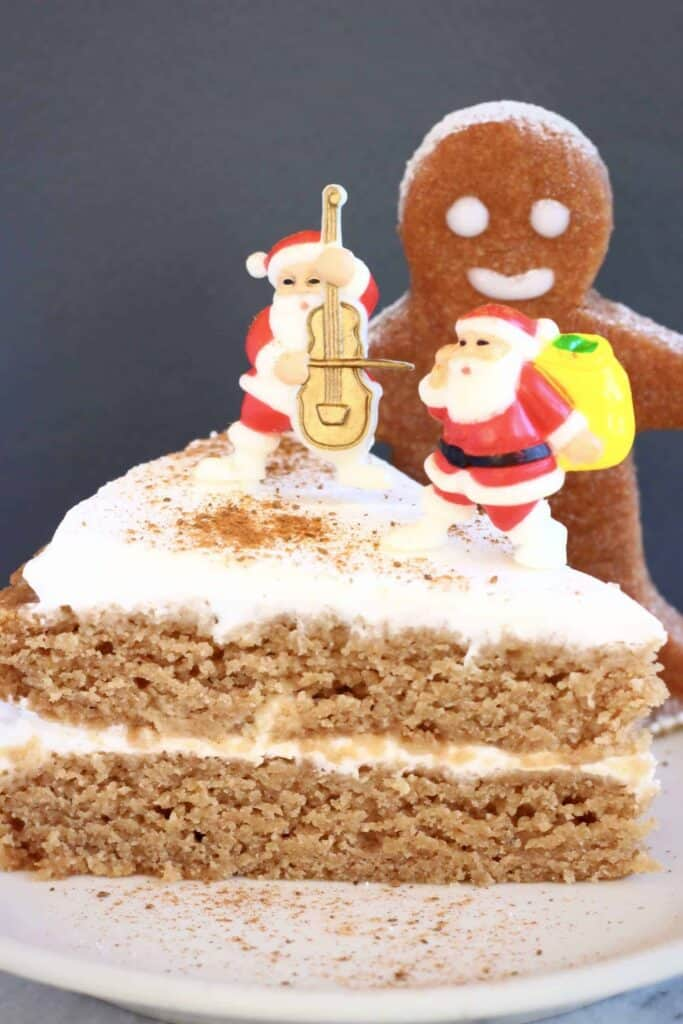 Photo of a slice of brown sponge cake sandwiched with white cream and decorated with plastic santa decorations with a gingerbread cookie behind against a grey background