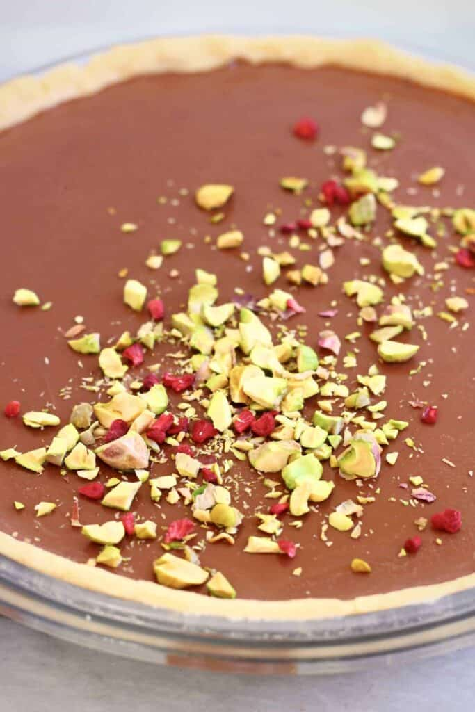 Photo of a chocolate tart topped with chopped pistachios and freeze-dried raspberries in a glass pie dish against a marble background