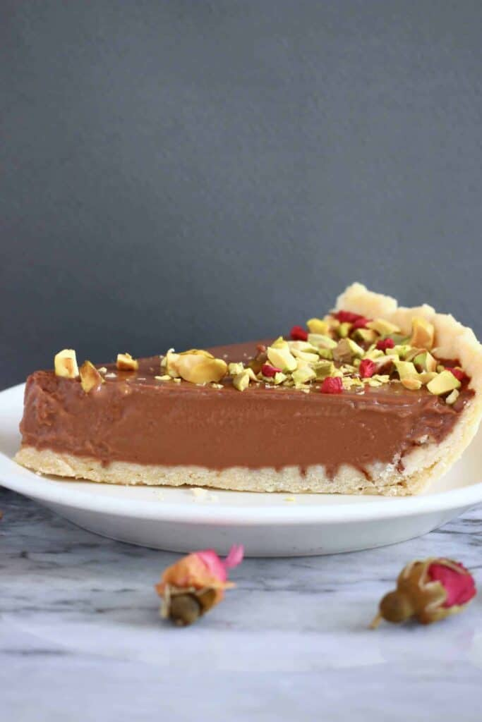 Photo of a slice of chocolate tart topped with chopped pistachios and freeze-dried raspberries on a white plate on a marble slab against a grey background