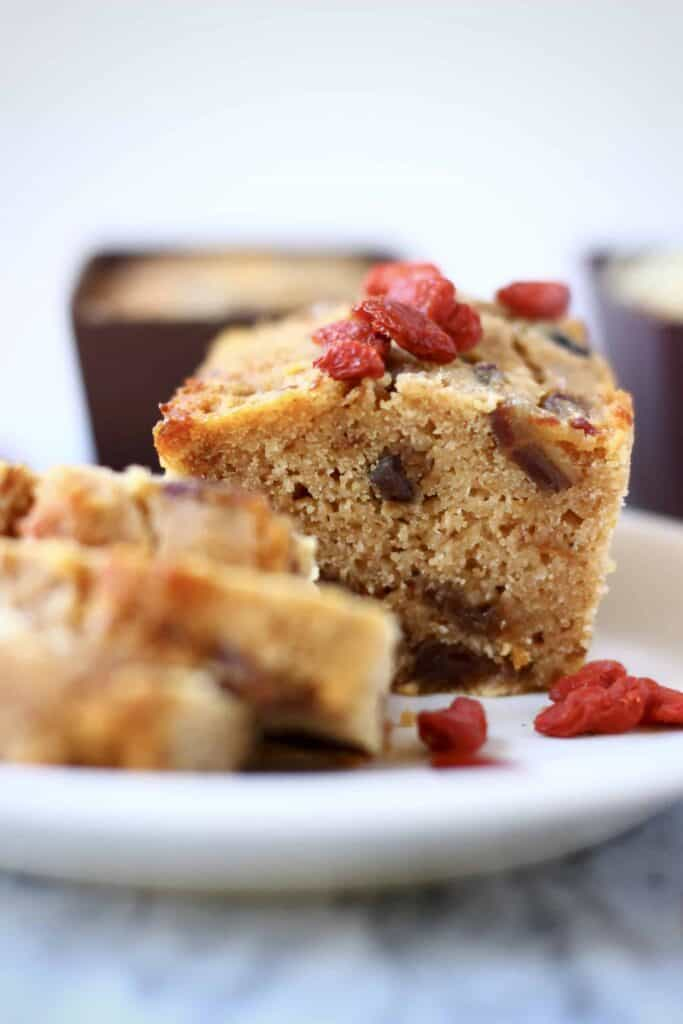 Photo of a small loaf of fruit cake with three slices taken from it on a white plate scattered with red goji berries with more mini loaves in the background