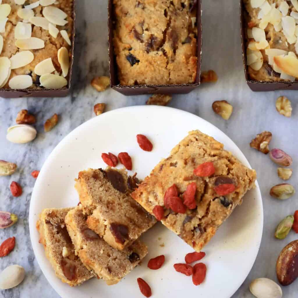 Photo of a small loaf of fruit cake with three slices taken from it on a white plate scattered with red goji berries with three mini loaves in the background